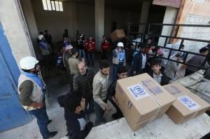 People unpack humanitarian aid from trucks in Duma
