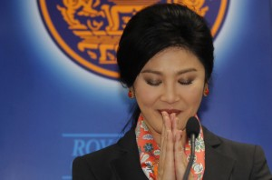 Thailand's Prime Minister Yingluck Shinawatra gives a traditional greeting as she addresses reporters in Bangkok