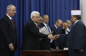 Palestinian Waqf and Religious Affairs Minister Idaeis shakes hands with Palestinian President Abbas during a swearing-in ceremony of the unity government, in the West Bank city of Ramallah