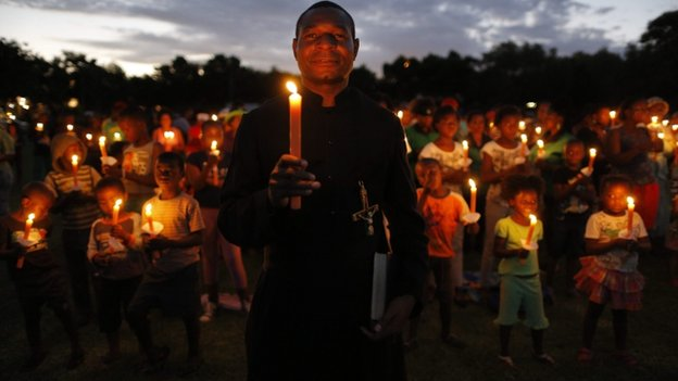 A priest carries a candle with hundreds of people during a memorial for the late Nelson Mandela in Soweto, Johannesburg, South Africa, 4 December 2014.
