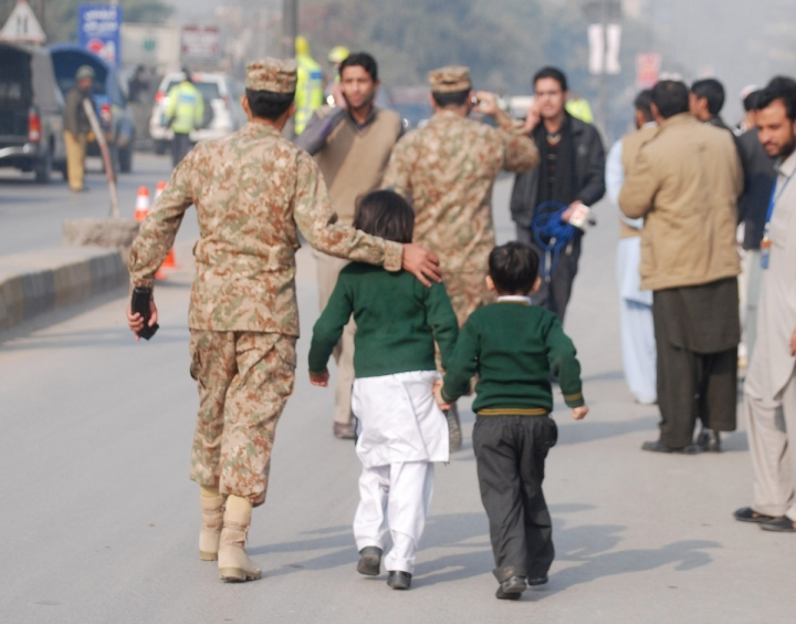 A soldier escorts schoolchildren after they were rescued from the Army Public School that is under attack by Taliban gunmen in Peshawar Reuters Photo: Khuram Parvez