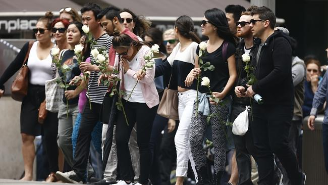 The grieving Lindt Cafe group walks up Martin Place to lay flowers at the scene of the violent siege which claimed their manager. Picture: Tim Hunter.
