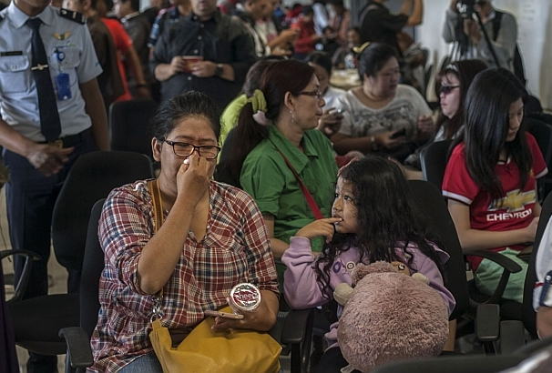 Relatives of passengers on board the missing AirAsia flight QZ8501 gather at Juanda airport in Indonesia.