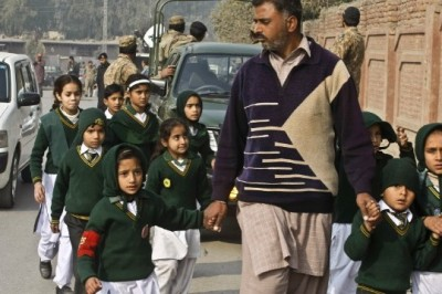 A man escorts students rescued from nearby school during a Taliban attack in Peshawar, Pakistan, Tuesday, Dec. 16, 2014. (AP Photo: Mohammad Sajjad)