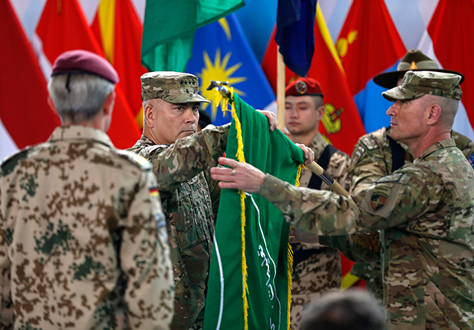 US General John Campbell, centre, folds the flag during the ceremony in Kabul.