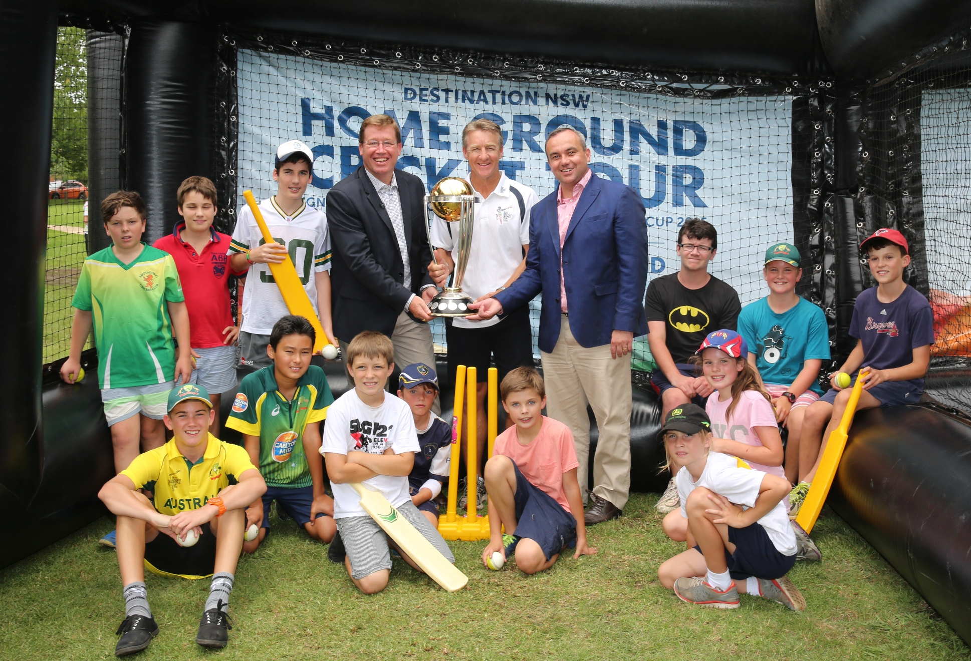 NSW Deputy Premier Troy Grant, former Australian cricketer Andy Bichel and Wollondilly MP Jai Rowell hold the ICC Cricket World Cup trophy, with encouragement from local cricketers.