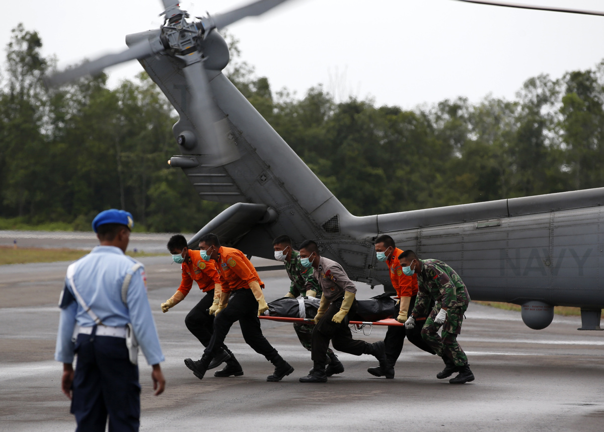The body of an AirAsia QZ8501 passenger is carried to an ambulance after being transported from a ship by a U.S. Navy helicopter from the USS Sampson at the airbase in Pangkalan Bun