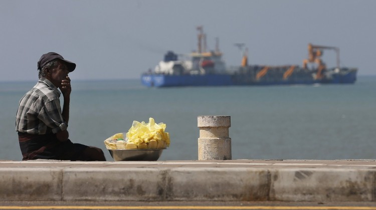 A vendor rests next to the Colombo Port City project. Photo: Dinuka Liyanawatte/Reuters