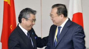 Japan's Deputy Minister of Foreign Affairs Shinsuke Sugiyama, left, and China's Assistant Foreign Minister Liu Jianchao, right, shake hands before their meeting in Tokyo.
