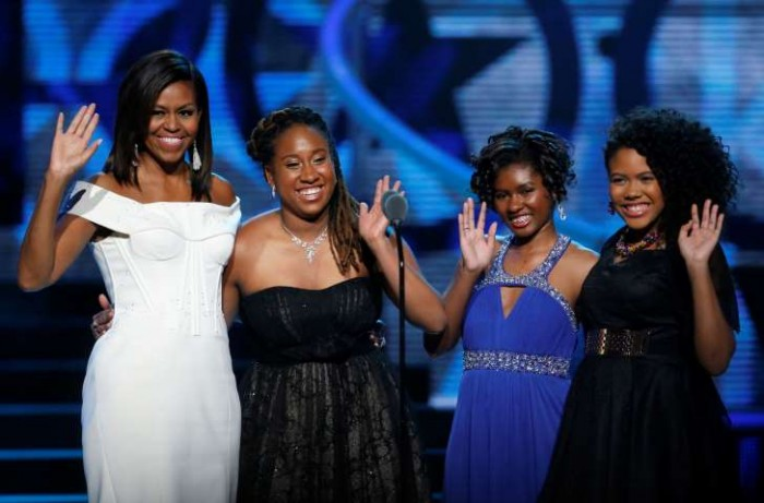 First Lady Michelle Obama, left, waves while standing on stage with Making A Difference award winners, from left, Kaya Thomas, Chental-Song Bembry and Gabrielle Jordan during a taping of the Black Girls Rock award. Photo: AP Photo/Julio Cortez