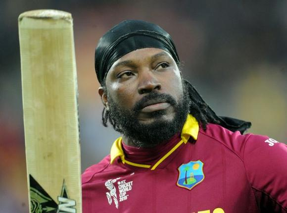West Indies star player Chris Gayle waves his bat to spectators while heading towards pavilion