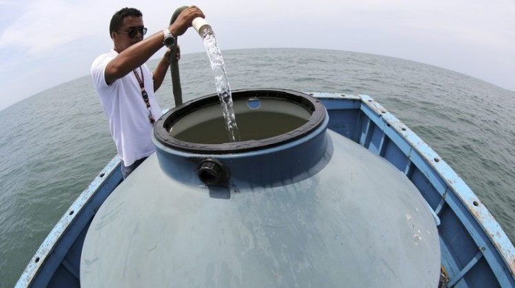 A man on a boat collects water from the ocean to be converted to drinking water through the process of desalination, in Bertioga.