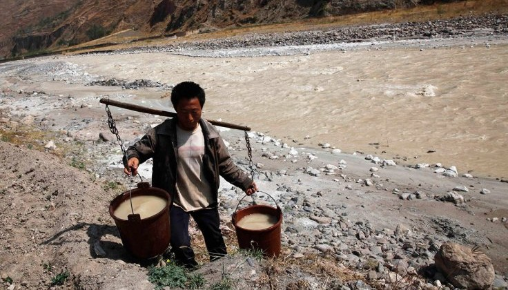 A villager carries buckets of drinking water from a polluted stream in Yunnan province, China. Photo: Reuters