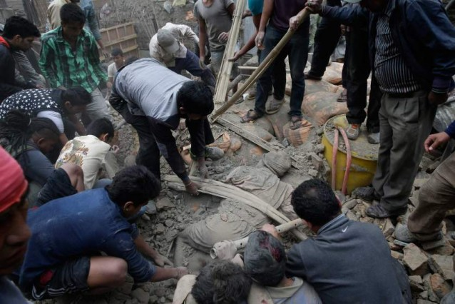 People try to free a man from the rubble of a destroyed building after an earthquake in Kathmandu, Nepal on April 25, 2015.