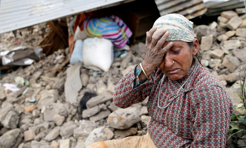 An elderly woman mourns in front of her destroyed home in the Kumalpur village, on the outskirts of capital Kathmandu.
