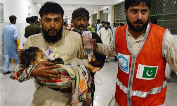 A man carries his injured daughter at a hospital following heavy rains and winds in Pakistan's city Peshawar on April 26, 2015