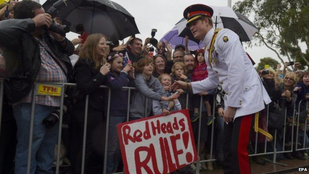 "Prince Harry meeting a crowd in Australia. A sign says ""red heads rule"". A sign saying ""red heads rule"" was displayed on a barrier"