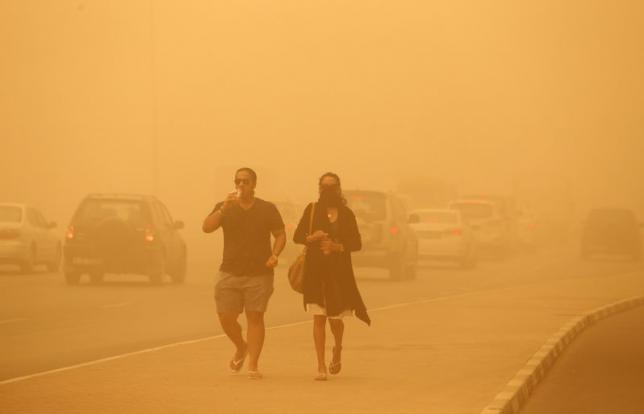 A woman walks with her face covered during a sand storm in Dubai April 2, 2015.  Photo: REUTERS/Ahmed Jadallah