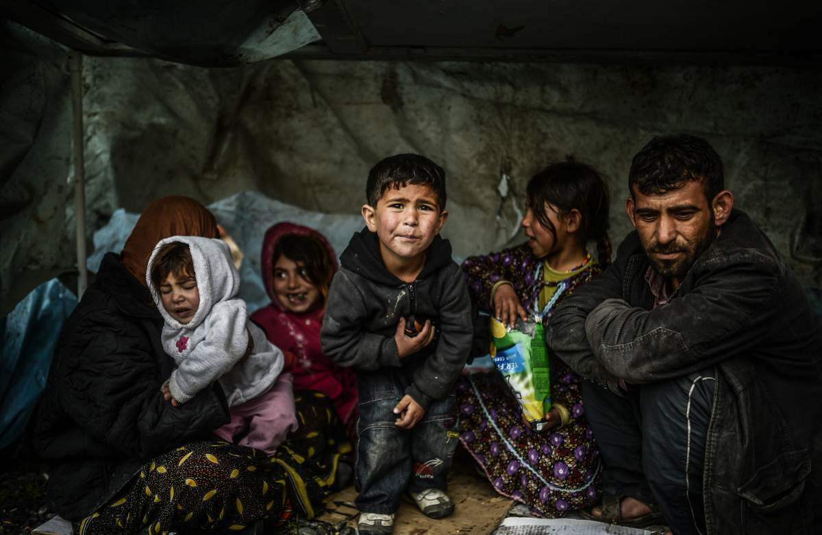 A Syrian refugee family from Aleppo stays under a shelter during a rainy day on March 8, 2014 in Uskudar, Istanbul. Photo: Bulent Kilic—AFP/Getty Images