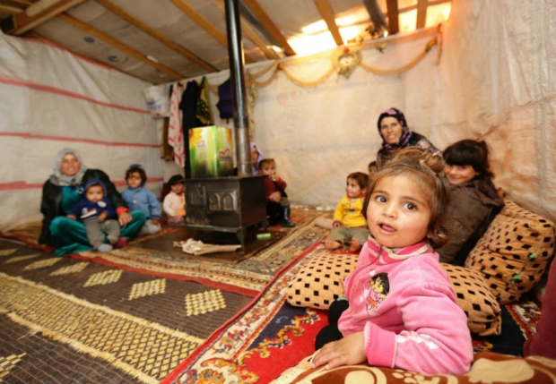 Umm Ali (right-back), the mother of eleven children and who is currently six-months pregnant sits by the 'sobia', a traditional Middle Eastern diesel or wood-powered stove with her children at an unofficial refugee camp in Jabaa, a village in the Bekaa Valley, Lebanon. — Photo: AFP