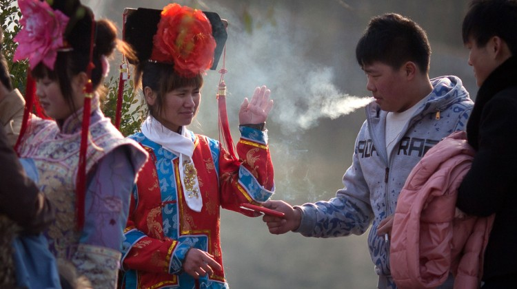 A tourists dressed in Qing dynasty style clothing waves away cigarette smoke in Beihai park in Beijing. Photo: Ed Jones/AFP via Getty Images