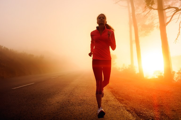 Healthy running runner woman early morning sunrise workout on misty mountain road workout jog. sunflare through the mist gives atmospheric feel and depth to these fitness images; Shutterstock ID 103383071; PO: aol; Job: production; Client: drone