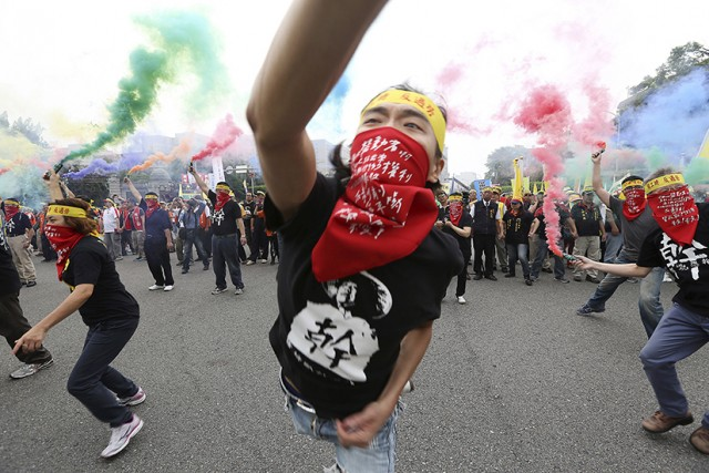 People throw smoke grenades during the annual Labour Day protest in front of Presidential Office in Taipei, Taiwan, May 1, 2015