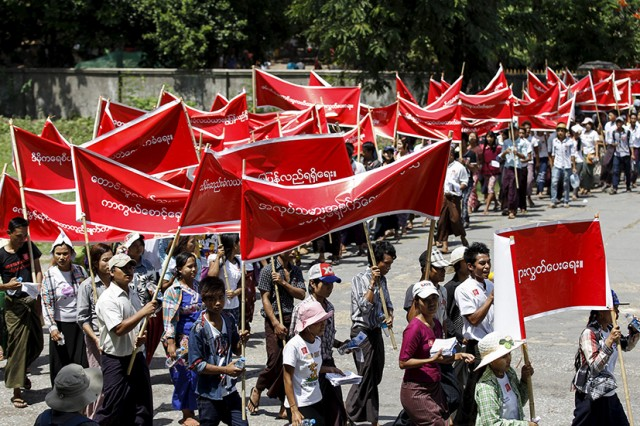 Workers carry banner with messages in support of workers' rights during a march to mark Labour Day in Yangon May 1, 2015