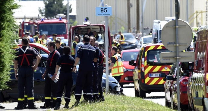 Police and firefighters gather at the entrance of Air Products and Chemicals, a gas factory near Lyon, France, on Friday June 26, after a terror attack.