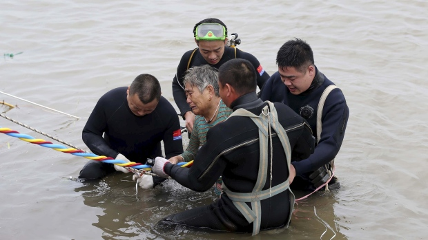 Divers pulle a 65-year-old woman from the hull of the passenger ship carrying 458 people that capsized on China's Yangtze River on Tuesday morning. (CNS photo via Reuters)