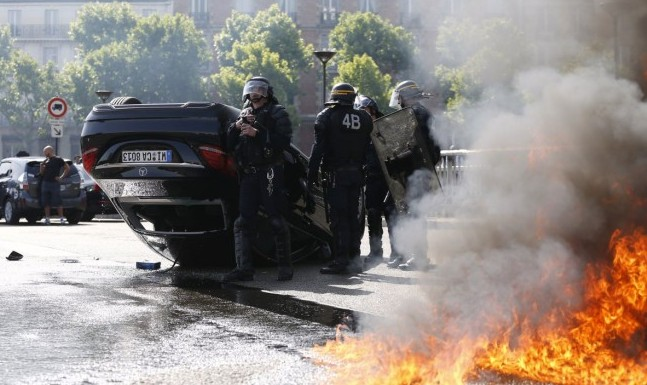 Riot police responded to protests in Paris after French taxi drivers overturned cars and set fire to tyres in protest against taxi app Uber