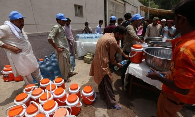 Water is distributed to people on a roadside in Karachi. Photograph: Rehan Khan/EPA