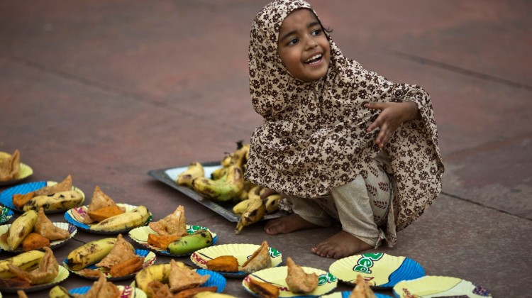 A girl arranges plates before iftar – the breaking-fast meal– during Ramadan at the Grand Mosque in Delhi, India. Photograph: Ahmad Masood/Reuters