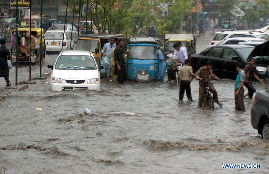 Vehicles move through a flooded street in southern Pakistan's Hyderabad on Sept. 9, 2012. (Xinhua/Janali)