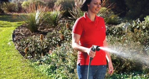 Woman watering the garden with a hose and trigger nozzle