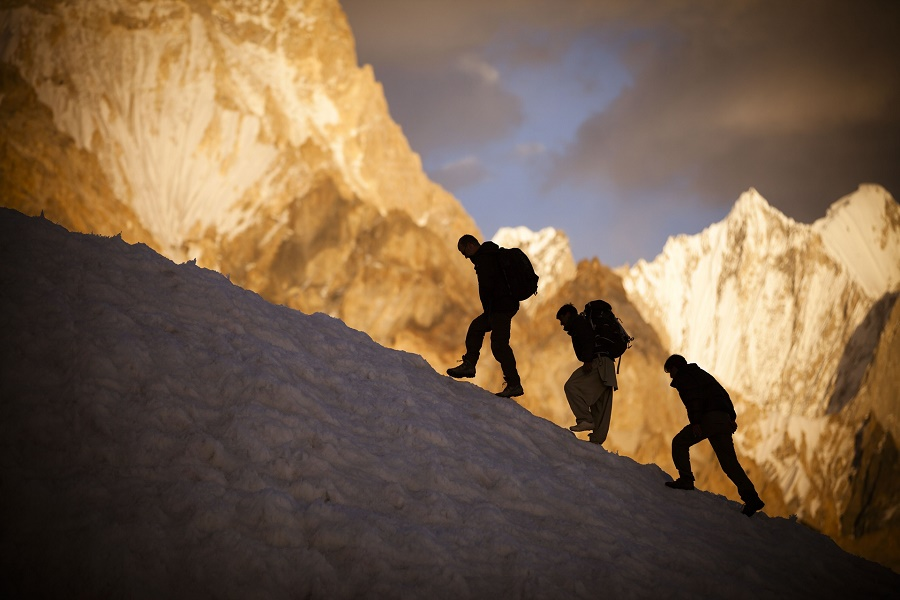 Expedition members meander between crevasses with the Gasherbrum IV massif visible in the background. PHOTO: DAVID KASZLIKOWSKI