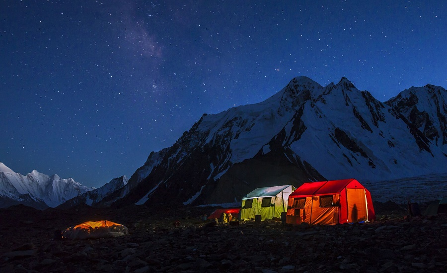The porters' tent at K2's base camp is just a tarpaulin stretched over the stones, left, while the other tents belong to expedition members. PHOTO: DAVID KASZLIKOWSKI