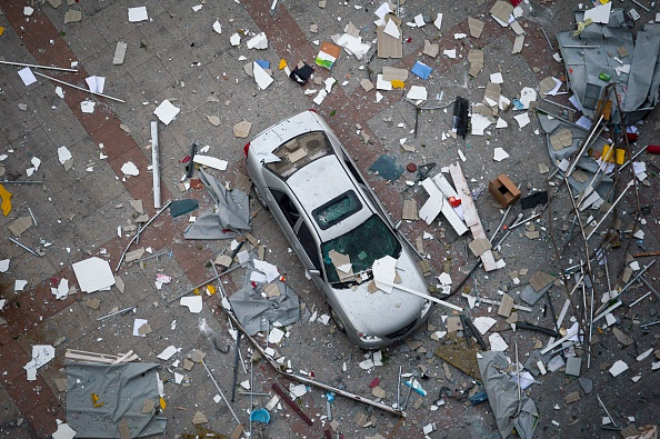 A damaged car is covered with shattered wall tiles and window parts at the site of the massive explosions in Tianjin on August 13, 2015. Enormous explosions in a major Chinese port city killed at least 44 people and injured more than 500, state media reported on August 13, leaving a devastated industrial landscape of incinerated cars, toppled shipping containers and burnt-out buildings. (Photo credit: STR/AFP/Getty Images)