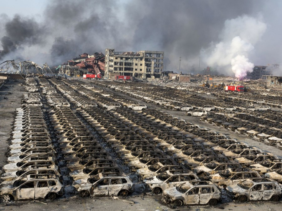 Smoke billows from the site of an explosion that reduced a parking lot filled with new cars to charred remains at a warehouse in Tianjin, China on Aug. 13, 2015. Ng Han Guan, AP