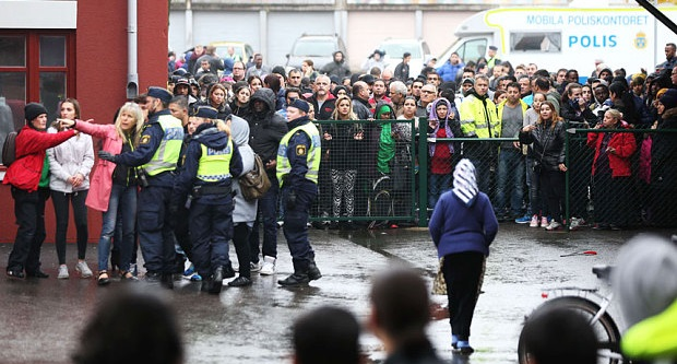 Swedish police officers speak to members of the public as they secure the area outside the school Photo: AFP/Getty Images