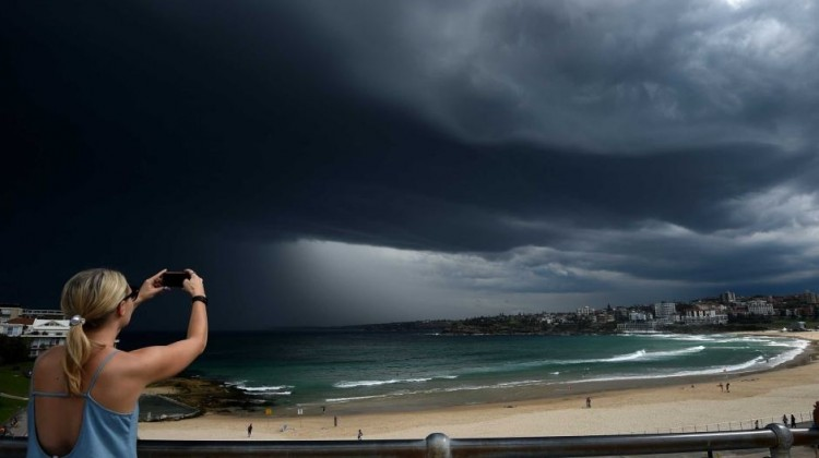 A woman photographs storm clouds over Bondi beach, with the BoM issuing a severe thunderstorm warning for Sydney. AAP Photo: Dan Himbrechts
