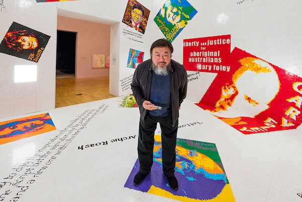 Ai Weiwei poses in his Letgo room – made of thousands of donated building bricks – at the National Gallery of Victoria.