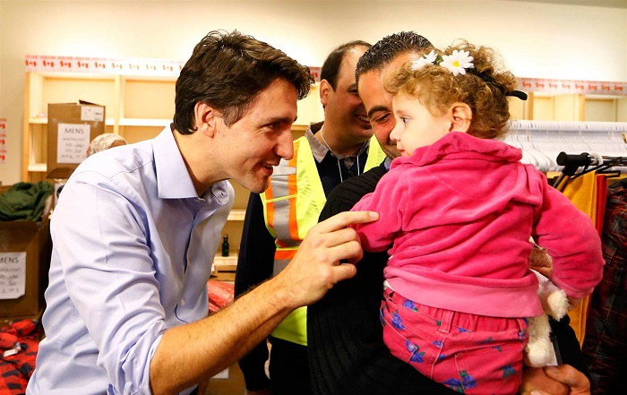 Canada's PM Justin Trudeau speaks with a young girl as he greets a family of Syrian refugees during their arrival at Pearson International airport, in Toronto, on Friday morning. (Nathan Denette/Canadian Press)