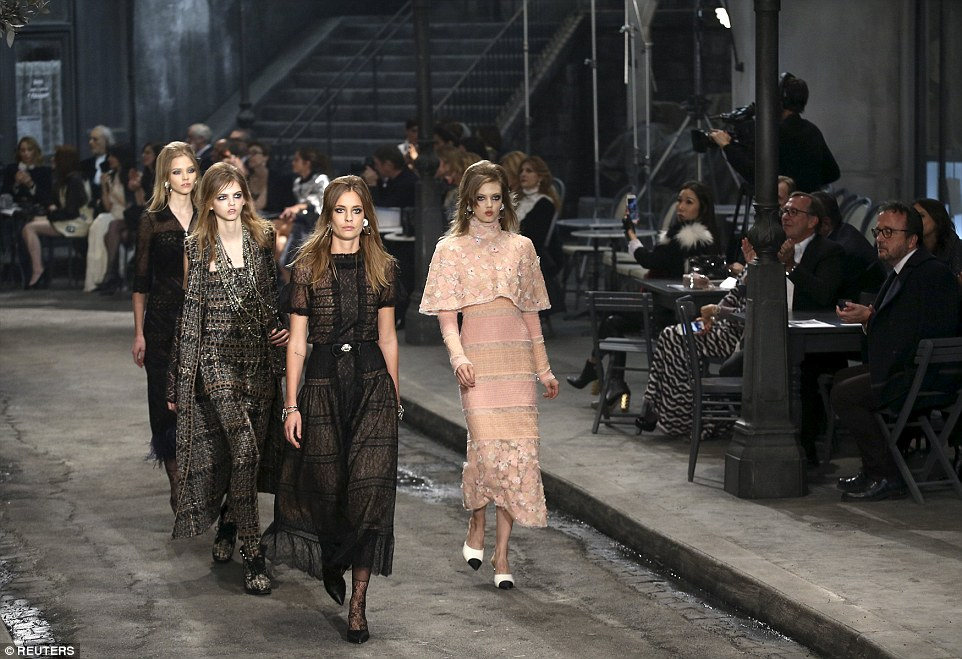 Some of the 800-strong audience applaud a quartet of models as they stroll along the catwalk pavement wearing some of the show's more feminine designs including centre, a black lace dress fitted at the waist with a bow and a pink dress with mini cape and long sleeves