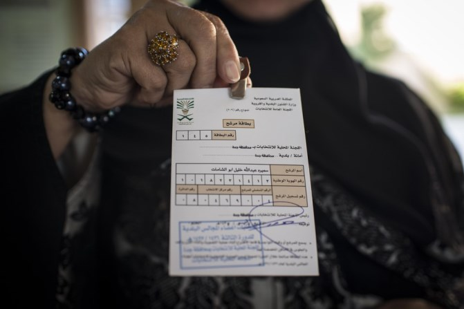 A woman holds up her election card, which is No. 1, indicating that she was the first to sign up at voting registration at a girls high school in North Jeddah on Saturday.