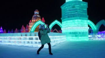 A woman uses a mobile phone to take a picture at the China Ice and Snow World on the eve of the opening ceremony of the Harbin International Ice and Snow Festival in Harbin, northeast China's Heilongjiang province on January 4, 2016. Over one million visitors are expected to attend the spectacular Harbin Ice Festival, where buildings of ice are bathed in ethereal lights and international ice sculptors compete for honours. AFP PHOTO / WANG ZHAOWANG ZHAO/AFP/Getty Images ORG XMIT:
