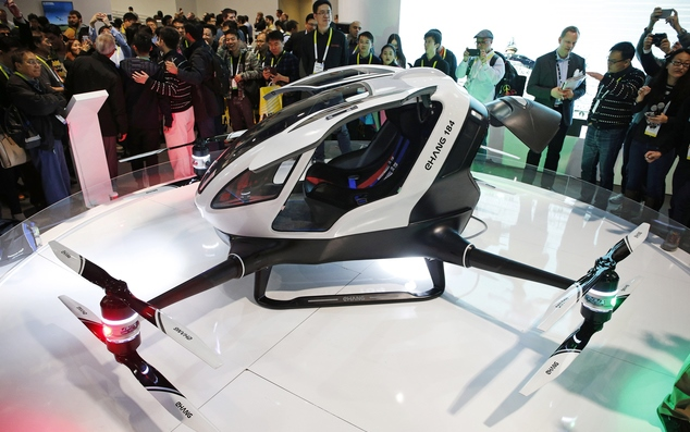 People crowd around the EHang 184 autonomous aerial vehicle at the EHang booth at CES International, Wednesday, Jan. 6, 2016, in Las Vegas.