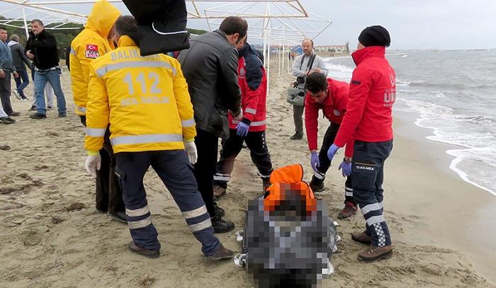 Turkish coast guards and medical team examine the dead migrants. (AA Photo)
