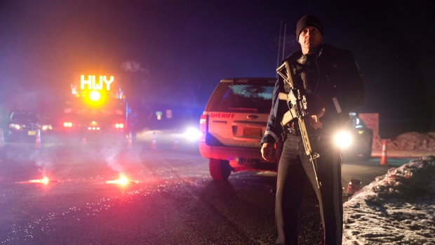Sgt. Tom Hutchison stands in front of an Oregon State Police roadblock on Highway 395 between John Day and Burns by Oregon State police officers Tuesday. (Dave Killen/The Associated Press)
