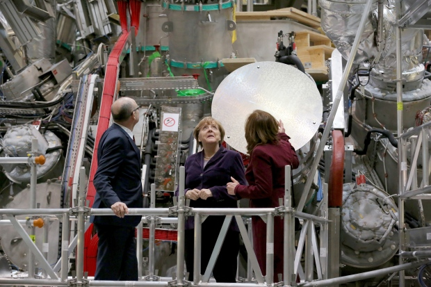 German Chancellor Angela Merkel, center, who holds a doctorate in physics, personally pressed the button at Wednesday's launch of an experiment they hope will advance the quest for nuclear fusion, considered a clean and safe form of nuclear power. AP Photo
